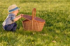 Litet barnbarn utomhus Årig en behandla som ett barn den bärande sugrörhatten för pojken som ser i picknickkorg Royaltyfria Foton