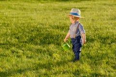 Litet barnbarn utomhus Årig en behandla som ett barn den bärande sugrörhatten för pojken som använder att bevattna kan Arkivfoton