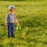 Litet barnbarn utomhus Årig en behandla som ett barn den bärande sugrörhatten för pojken som använder att bevattna kan Royaltyfria Bilder