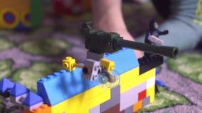 Litet barnbarnpys med blondihårsammanträde som omges, genom leksaker och att spela med diagramet för lego för byggnadskvarter det stock video