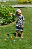Litet barnflicka 'fiske 'på den solbelysta sommargräsmattan arkivfoto