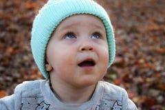 Litet barnflicka i blå hatt som stirrar på himlen Royaltyfria Bilder