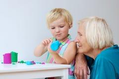 Litet barnflicka med farmodern som skapar från plasticine Fotografering för Bildbyråer