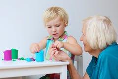Litet barnflicka med farmodern som skapar från plasticine Arkivbilder