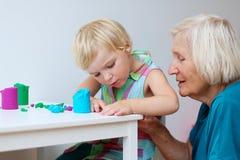 Litet barnflicka med farmodern som skapar från plasticine Royaltyfria Bilder