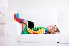 Litet barnflicka med minnestavlaPC Arkivfoto