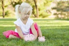 Litet barnflicka med två spargrisar utomhus Royaltyfria Foton