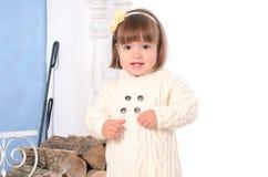 Litet barnflicka nära vedtrave arkivfoto