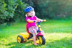 Litet barnflicka på en cykel Fotografering för Bildbyråer