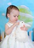 Litet barnflicka som daltar kaninen på easter Arkivbilder