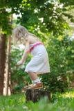 Litet barnflicka som hoppar ner från trädstubbe tillbaka Fotografering för Bildbyråer