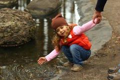Litet barnflicka som kontrollerar vatten i parkeradammet fotografering för bildbyråer