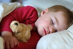 Litet barnflicka som sover i säng Fotografering för Bildbyråer
