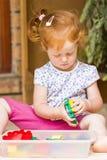 Litet barnflicka som spelar leksaker Arkivbild