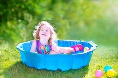Litet barnflicka som spelar med bollar i trädgården Royaltyfri Bild