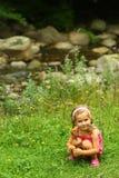 Litet barnflicka som upp väljer lösa blommor nära bergfloden royaltyfri bild