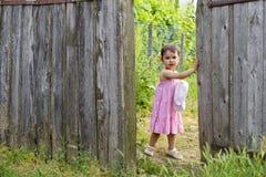 Litet barnflickan öppnar trägrindporten Arkivfoto