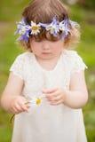Litet barnflickan med en krans av blommor gissar på en kamomill royaltyfria bilder