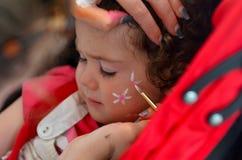 Litet barnflickan som får hennes framsida, målade vid framsidamålningkonstnären Fotografering för Bildbyråer