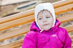 Litet barnflickasammanträde på bänken Royaltyfria Bilder