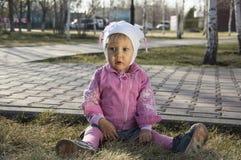 Litet barnflickasammanträde på jordningen Royaltyfri Fotografi