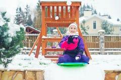 Litet barnflickasammanträde på sladen som är klar att spela, kastar snöboll kamp Arkivbilder