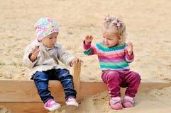 Litet barnflickor som spelar i sand royaltyfria foton