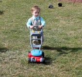 Litet barnpojke i en dräkt som skjuter en gräsklippare Royaltyfri Fotografi