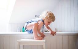 Litet barnpojke i ett farligt läge i badrummet arkivfoto