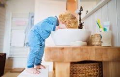 Litet barnpojke i ett farligt läge i badrummet royaltyfria foton