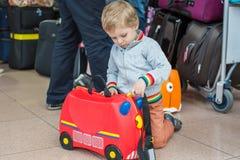 Litet barnpojke med den röda barnresväskan på flygplatsen royaltyfri fotografi