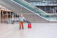 Litet barnpojke med den röda barnresväskan på flygplatsen Royaltyfria Bilder