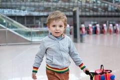 Litet barnpojke med den röda barnresväskan på flygplatsen Arkivbild