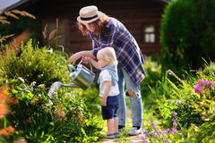 Litet barnpojke och hans unga moder som bevattnar växter i trädgården Royaltyfria Bilder