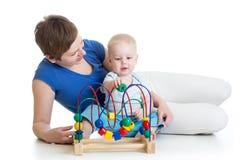 Litet barnpojke och mamma som spelar med den bildande leksaken Arkivbild