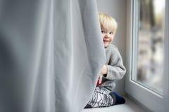 Litet barnpojke på fönsterfönsterbrädan Arkivfoton