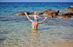 Litet barnpojke på faders skuldror på stranden arkivfoton