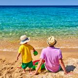 Litet barnpojke på stranden med fadern royaltyfria foton