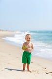 Litet barnpojke på stranden med godisen Royaltyfri Bild