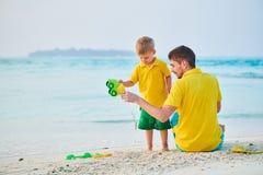 Litet barnpojke p? stranden med fadern arkivfoton