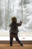 Litet barnpojke som är stående upp mot ett fönster som ut ser Arkivbilder
