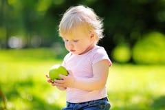 Litet barnpojke som äter det nya gröna äpplet royaltyfria bilder