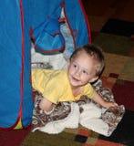 Litet barnpojke som campar ut i ett tält i uppehälleroen Arkivbild