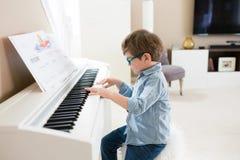 Litet barnpojke som hemma spelar pianot royaltyfria foton