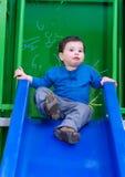 Litet barnpojke som ler på en glidbana Royaltyfria Bilder