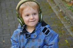Litet barnpojke som lyssnar till musik arkivfoto