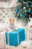 Litet barnpojke som öppnar en ask med julgåvan Arkivfoto