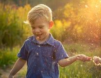 Litet barnpojke som spelar i sommarsol Arkivbild