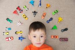 Litet barnpojke som spelar med bilsamlingen på matta Trans.-, flygplan-, nivå- och helikopterleksaker för barn Royaltyfri Fotografi
