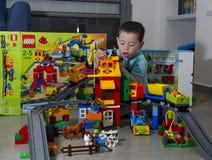 Litet barnpojke som spelar med den LEGO-duplodrevet och lantgården Arkivbilder